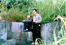 Master Tham with his master studying the fantastic Feng Shui of a grave yard while in China.